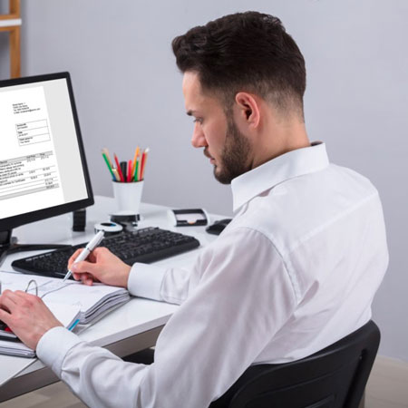 Human sitting at table holding sheet of paper