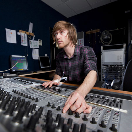 Human at mixing board with fingers on dial
