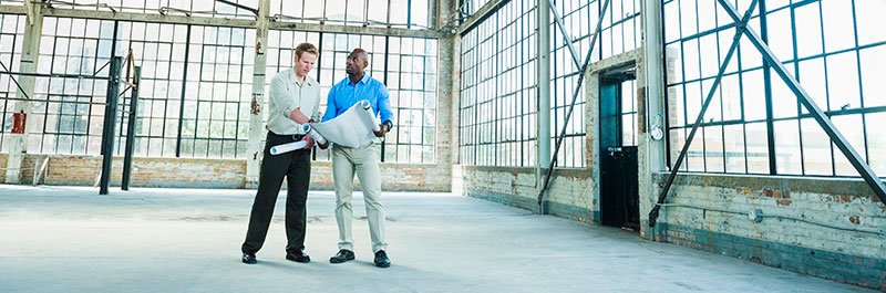 two men standing in an empty warehouse