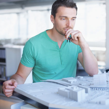 Human stares intently at model buildings